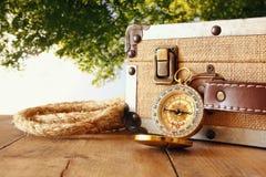 Reisendweinlesegepäck und -kompaß auf Holztisch Stockfotografie
