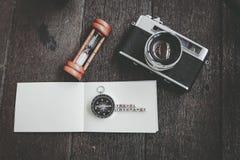 REISEVERSICHERUNG, Weinlesekamera und Kompass auf hölzernem Hintergrund Lizenzfreies Stockfoto