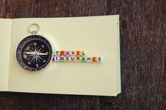 REISEVERSICHERUNGS-Wortblock auf gelbem Papier mit Kompass vorbei flehen an Lizenzfreie Stockfotografie