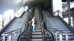 Reisezusammenfassung, asiatischer Reisender mit Rucksack auf der Rolltreppe des öffentlichen Transports stock footage