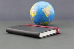 Reisgeheugen in zwarte dagboek en bol wordt weerspiegeld die Royalty-vrije Stock Foto