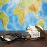 Reisgeld in kruik, zonnebril, wereldkaart bij achtergrond Royalty-vrije Stock Foto