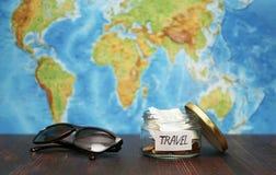 Reisgeld in kruik, zonnebril, wereldkaart bij achtergrond Stock Afbeelding