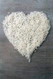 Reiskörner bildeten sich in der Herzform auf hölzernem Hintergrund Lizenzfreie Stockbilder