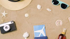 Reiskaartjes, camera en hoed op strandzand stock videobeelden