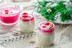 Reispudding mit Mandeln, Schlagsahne und Kirsche sauce Stockfotos