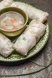 Reisrollen mit Gemüse und Huhn auf einer grünen Platte mit Gemüsesuppe auf hölzernem rustikalem Hintergrundabschluß oben Lizenzfreies Stockfoto