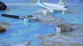 Reistoebehoren en stuk speelgoed vliegtuig op de achtergrond van de wereldkaart, vakantie planning stock video