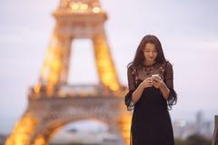 Reisvrouw die smartphone gebruiken dichtbij de toren van Eiffel en de carrousel, Parijs Het gelijk maken van weinig lawaaierig be stock afbeelding