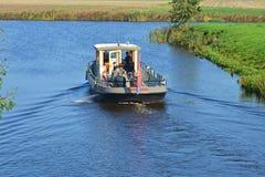 Reitdiepveeren med passagerare som seglar över Reitdiepen i Groningen Arkivfoto