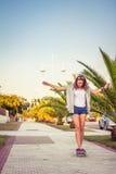 Reiten des jungen Mädchens in einem Skateboard draußen an Lizenzfreie Stockbilder
