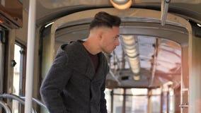 Reiten des jungen Mannes auf Tram oder altem Bus in der Stadt stock video footage