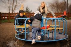 Reiten des kleinen Jungen auf dem Karussell mit jungen Eltern stockbild