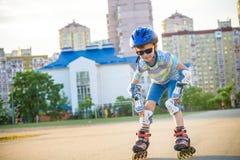 Reiten des kleinen Jungen auf Rollen im Sommer im Park Glücklicher ch lizenzfreies stockbild
