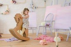 Reiten des kleinen Mädchens auf einem Papierpferd Lizenzfreie Stockfotos