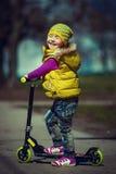 Reiten des kleinen Mädchens auf einem Roller Stockfotos
