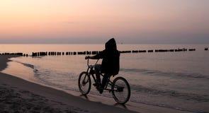 Reiten eines Fahrrades während des Sonnenaufgangs Stockfotografie