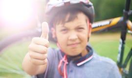 Reiten ist Super Porträt des lächelnden Jugendlichreitfahrrades und der geben Daumen oben auf Hintergrund des Parks und des Fahrr stockfotografie