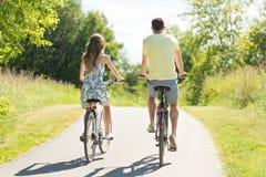 Reitenfahrräder der jungen Paare im Sommer lizenzfreies stockbild