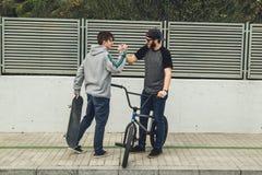Reitenfahrräder und Skateboards der jungen Leute in der Stadt Kerle mit einem Rochen und einem bmx hinunter die Straße lizenzfreies stockfoto