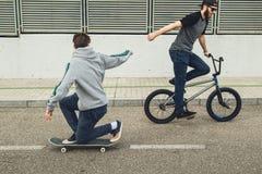 Reitenfahrräder und Skateboards der jungen Leute in der Stadt Kerle mit einem Rochen und einem bmx hinunter die Straße stockbild