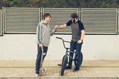 Reitenfahrräder und Skateboards der jungen Leute in der Stadt Kerle mit einem Rochen und einem bmx hinunter die Straße stockbilder