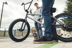 Reitenfahrräder und Skateboards der jungen Leute in der Stadt Kerle mit einem Rochen und einem bmx hinunter die Straße stockfotos