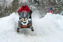 Reiter, die ein Schneemobil fahrung fliegen stockfotos