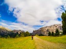 Reitroute einer Frau, in Richtung zu Val Gardena, unter den felsigen Bergen der Dolomit, des trentino, des Italiens und der grüne stockbild
