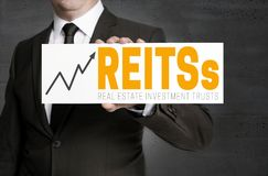 REITs sign is held by businessman. Concept Stock Images