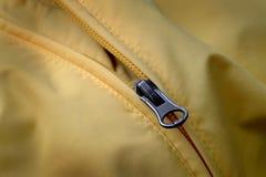 Reißverschluss auf gelbem Mantel mit Beschaffenheit Stockfoto