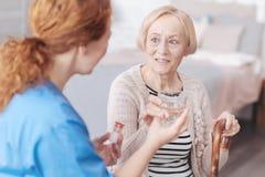 Reizend ältere Dame, die Pflegekraft beim Nehmen des Wassers betrachtet lizenzfreie stockbilder