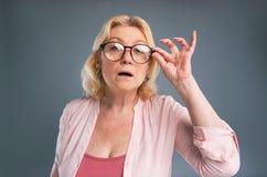 Reizend ältere Frau, die ihre Brillen justiert lizenzfreie stockfotografie