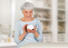 Reizend ältere Frau, die zu Hause kosmetische Creme auf ihrem Gesicht für Gesichtshautpflege im Badezimmer aufträgt Lizenzfreies Stockfoto