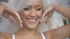 Reizend attraktive blonde Braut mit hübschem Lächeln und Make-up wirft unter dem Schleier auf Schließen Sie herauf Portrait stock video footage