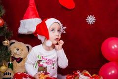 Reizend Baby, das von den Weihnachtsgeschenken träumt Lizenzfreie Stockfotografie