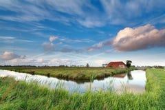 Reizend Bauernhaus durch Fluss über blauem Himmel Stockbild