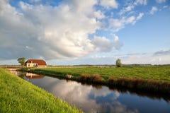 Reizend Bauernhaus, Fluss und blauer Himmel Lizenzfreies Stockbild