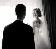 Reizend blonde Braut betrachtet über ihrer Schulter Bräutigam Stockfotografie