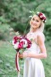 Reizend blonde Braut mit zartem Herbst blüht in ihrem Haar Lizenzfreie Stockbilder