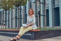 Reizend blonde Frau in der modernen Kleidung, studierend mit einem Buch und sitzen auf einer Bank im Park gegen einen Wolkenkratz Lizenzfreie Stockfotografie