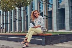 Reizend blonde Frau in der modernen Kleidung, studierend mit einem Buch und sitzen auf einer Bank im Park gegen einen Wolkenkratz Stockfotografie