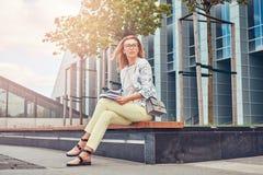 Reizend blonde Frau in der modernen Kleidung, studierend mit einem Buch und sitzen auf einer Bank im Park gegen einen Wolkenkratz Stockbilder