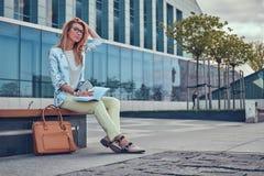 Reizend blonde Frau in der modernen Kleidung, studierend mit einem Buch und sitzen auf einer Bank im Park gegen einen Wolkenkratz Lizenzfreie Stockbilder