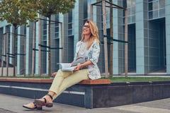 Reizend blonde Frau in der modernen Kleidung, studierend mit einem Buch und sitzen auf einer Bank im Park gegen einen Wolkenkratz Stockfoto
