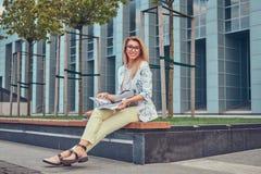 Reizend blonde Frau in der modernen Kleidung, studierend mit einem Buch und sitzen auf einer Bank im Park gegen einen Wolkenkratz Lizenzfreies Stockfoto
