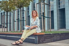 Reizend blonde Frau in der modernen Kleidung, studierend mit einem Buch und sitzen auf einer Bank im Park gegen einen Wolkenkratz Stockbild