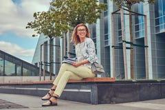Reizend blonde Frau in der modernen Kleidung, studierend mit einem Buch und sitzen auf einer Bank im Park gegen einen Wolkenkratz Lizenzfreies Stockbild