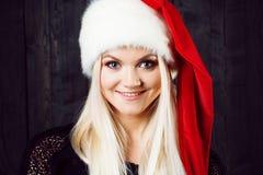 Reizend blonde Frau in der Weihnachtskappe Dunkler hölzerner Hintergrund Lizenzfreies Stockbild