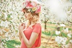 Reizend blonde Frau, die in den Obstgarten geht Lizenzfreie Stockbilder